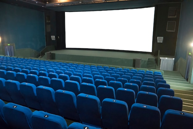 Empty movie cinema with rows of blue seats and white isolated screen