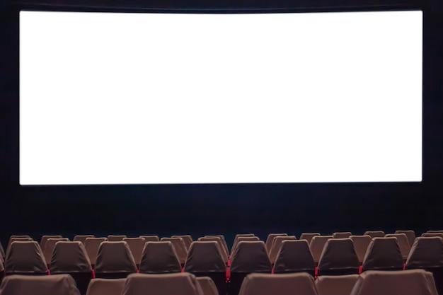 Пустой киноэкран с размытым стулом в кинотеатре.