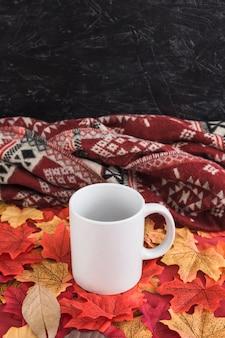 Empty mug on leaves near blanket