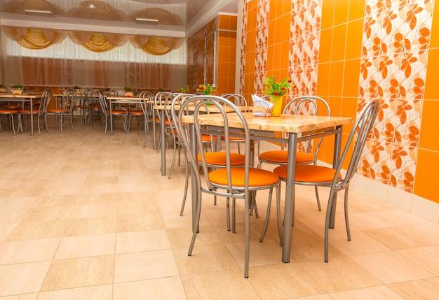 大きな学校の食堂の空の新しいテーブル