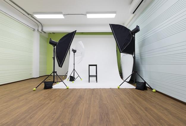 空の誰も屋内の部屋のスタジオの白い写真撮影シーンとプロの写真家の機器は、モデルの準備ができている黒い椅子と三脚スタンドにソフトボックスストロボフラッシュ傘リフレクター電球を設定しました。