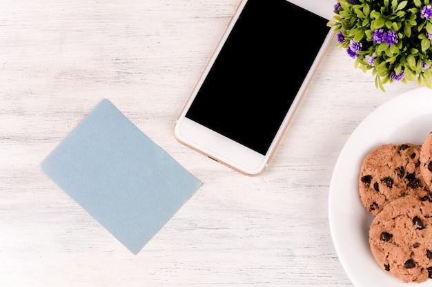 커피, 쿠키 및 휴대 전화와 함께 빈 메모 지