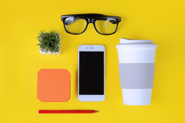 커피, 펜, 전화 및 안경의 플라스틱 컵 빈 메모 지