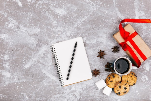 Empty notebbok lies before cup of coffee, present box and delicious cookies