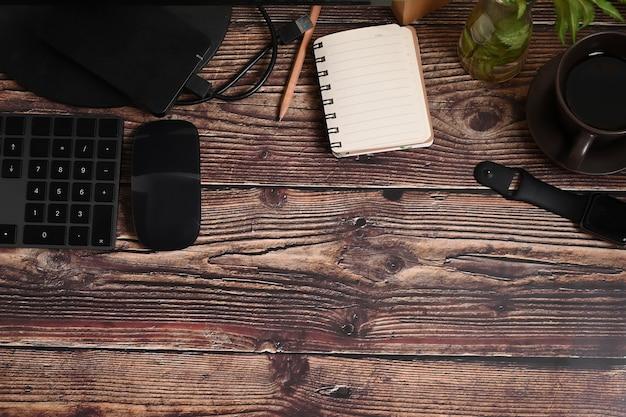 Пустой блокнот и черное оборудование на деревянном столе.