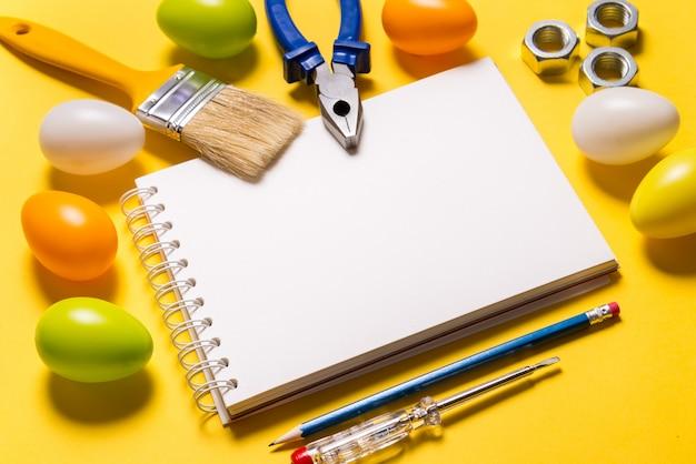 Пустой блокнот и инструменты строителя на желтом столе, концепция пасхи