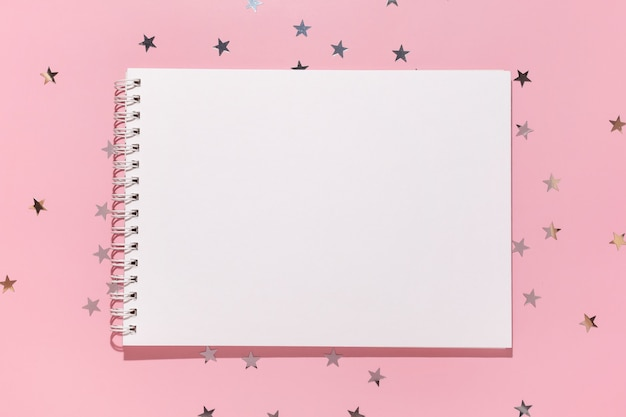 Пустой блокнот и звезды конфетти льются на пастельный розовый фон, вид сверху. плоская планировка. концепция праздника, приветствия или хороших новостей. шаблон макета. вид сверху. пустой блокнот