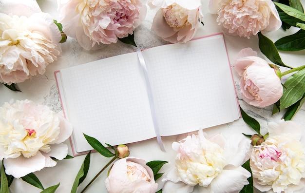 空のノートブックとピンクの牡丹の花