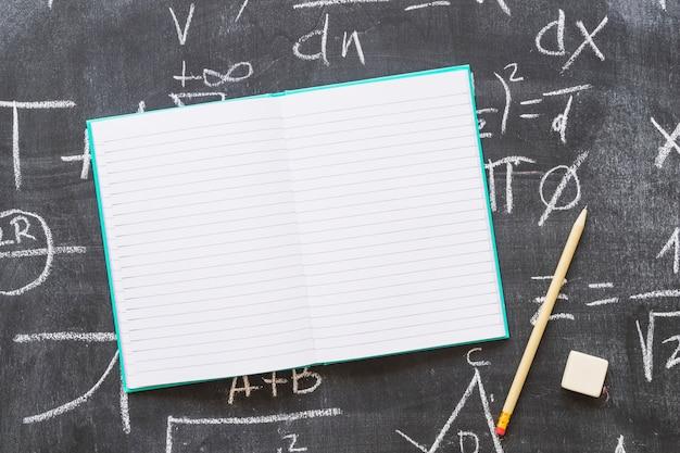 Empty notebook on blackboard with pen