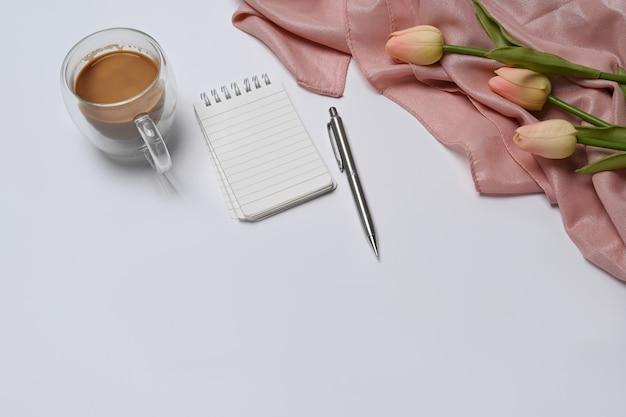 Пустой блокнот, кофейная чашка и розовые тюльпаны на белом столе.