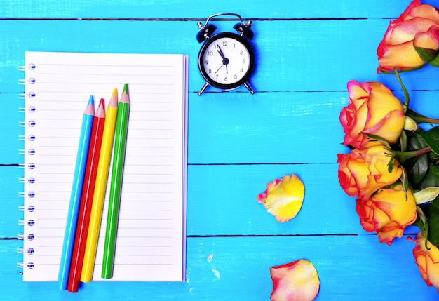 Empty notebook and colorful pencils