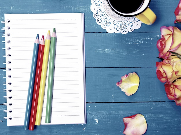Empty notebook and colorful wooden pencils