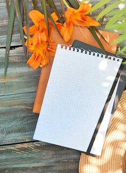 Пустой блокнот плоский макет с цветами лилии на деревянном столе