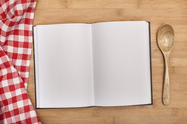 Пустой блокнот для рецептов с ложкой и скатертью на деревянном столе