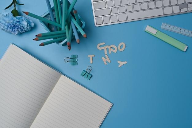 파란색 배경에 빈 노트북, 키보드 및 연필 홀더.