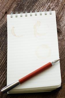 펜과 커피 얼룩이있는 빈 노트북 줄 지어 페이지 프리미엄 사진