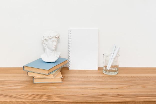 Пустая тетрадь на деревянном столе с книгами и маленькой гипсовой скульптурой давида