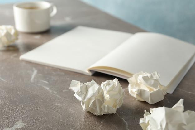 Пустой блокнот, бумажные шарики и чашка кофе на сером столе, крупным планом