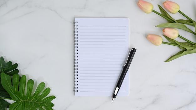 Пустой блокнот, ручка и розовые тюльпаны на мраморном фоне.