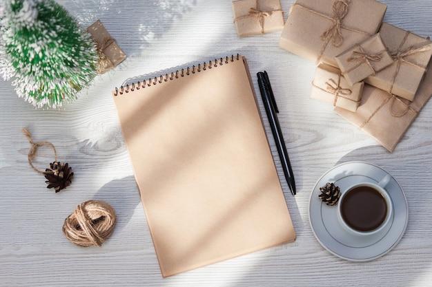 Пустой блокнот, ручка, коробки для упаковки ремесел, плоская планировка, вид сверху.