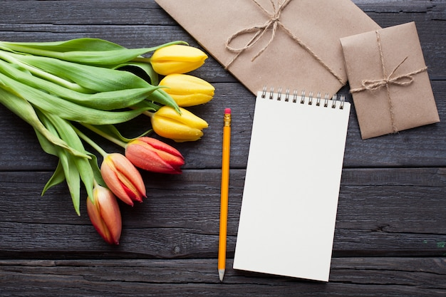 Empty notebook, pencil and yellow tulips.