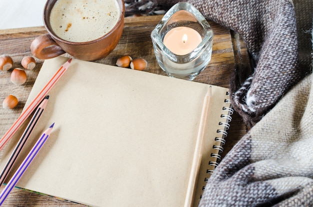 Empty notebook, plaid, candle and coffee cup