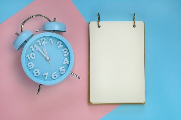 Empty notebook with a blue alarm clock on a paper combined background