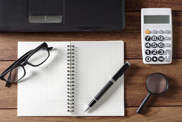 Пустой ноутбук с калькулятором и ноутбуком на рабочем столе