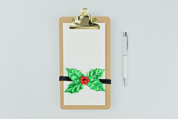 Empty notebook with christmas decor and pen on white