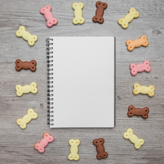 Empty notebook with dog snacks around