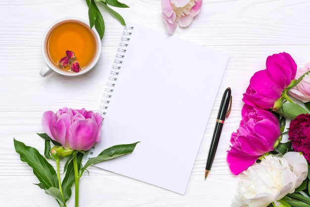 Empty notebook with place for text, pen, a cup of tea and peonies flowers on a white wooden background.