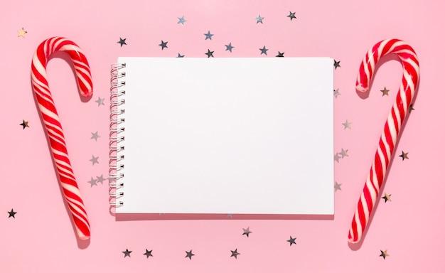 Пустой блокнот с красными рождественскими конфетами и звездами конфетти льется на пастельный розовый фон, вид сверху. плоская планировка. праздник новый год, приветствие или концепция хороших новостей. шаблон макета. пустой блокнот
