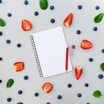 Empty notebook with strawberries and blueberries on grey background