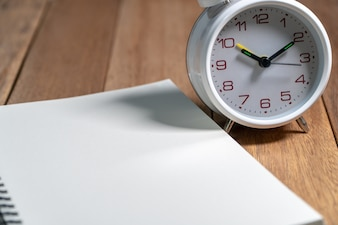 Empty notebook with white vintage alarm clock on the wooden table.