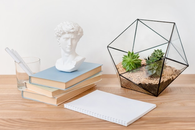 Empty notebook on wooden table with books, succulent plants and small david plaster sculpture