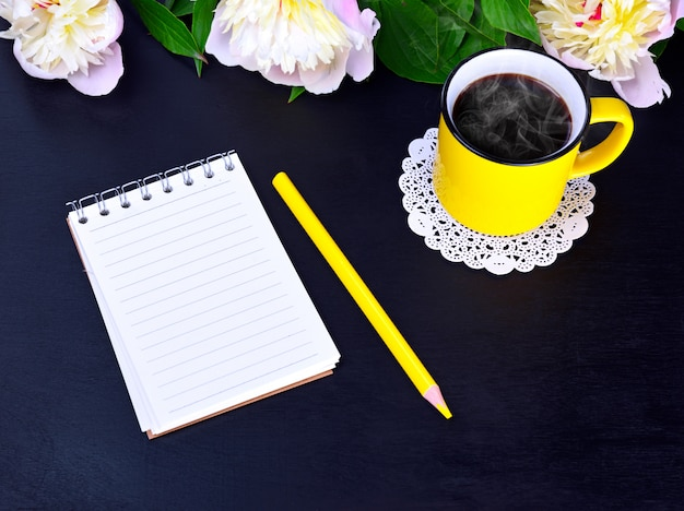 Empty notebook and yellow mug with hot coffee