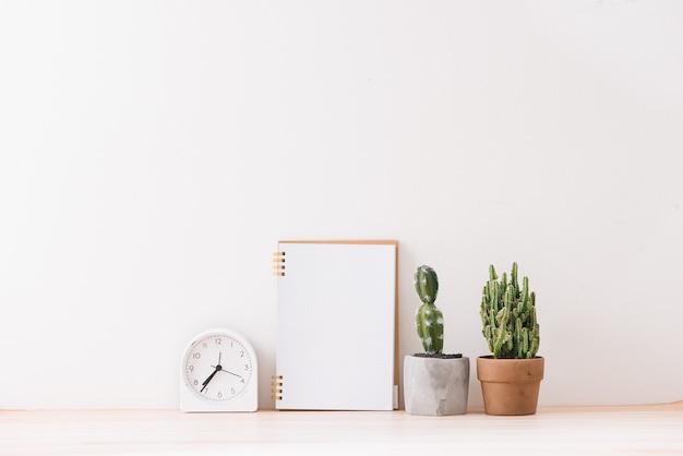 Пустые тетради на белом фоне с кактусом, белый будильник