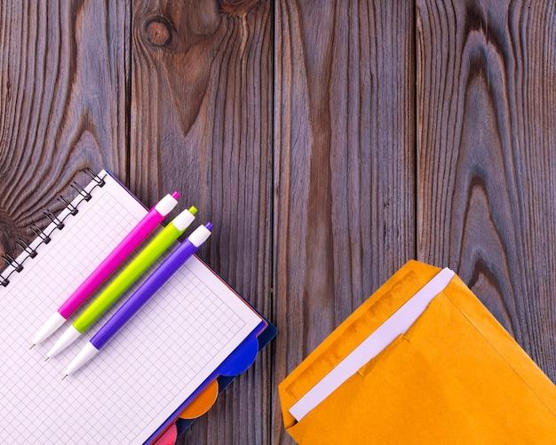 空のメモ帳と木の表面とペンの黄色い封筒。フラットレイ