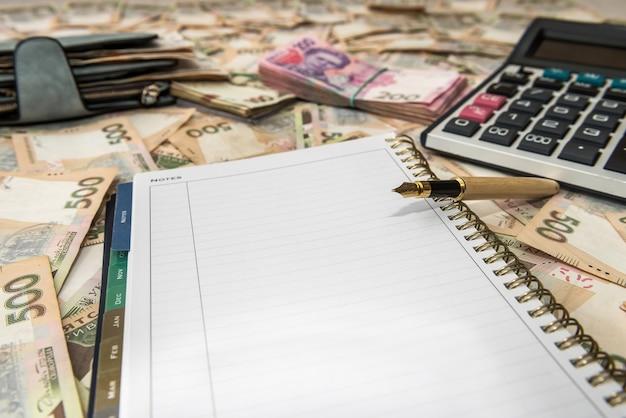 빈 메모장, 우크라이나어 돈 배경에 계산기로 돈의 전체 지갑
