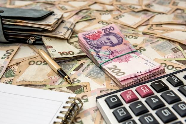 Пустой блокнот, полный бумажник денег с калькулятором на украинском денежном фоне. 500 банкнот. гривна (uah). вид сверху.