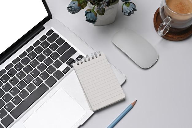 Пустой блокнот, портативный компьютер и кофейная чашка на белом офисном столе.