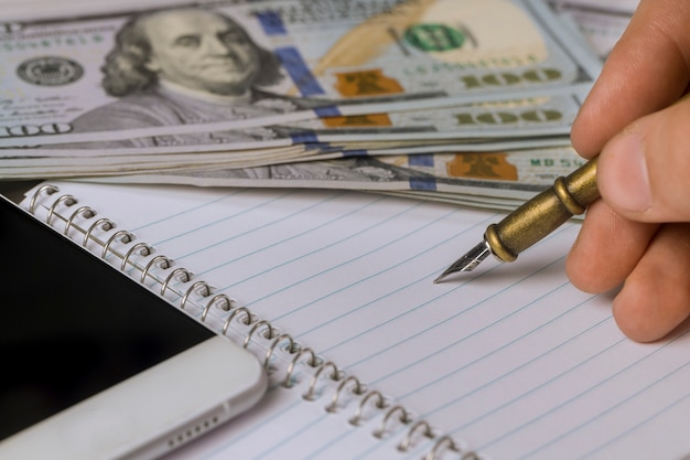 Empty notepad on man hand writes dollar banknotes with pen