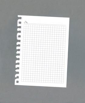 Пустой список бумаги блокнота на сером фоне
