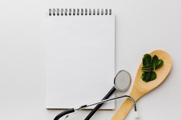 Empty notepad surrounded by stethoscope and spoon top view