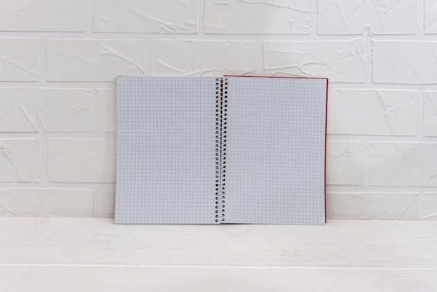 Empty notepad on white brick wall background