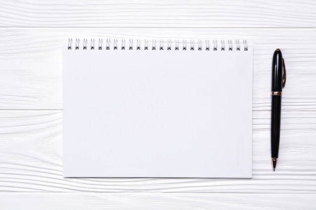 Empty notepad with place for text and pen on a white wooden background.
