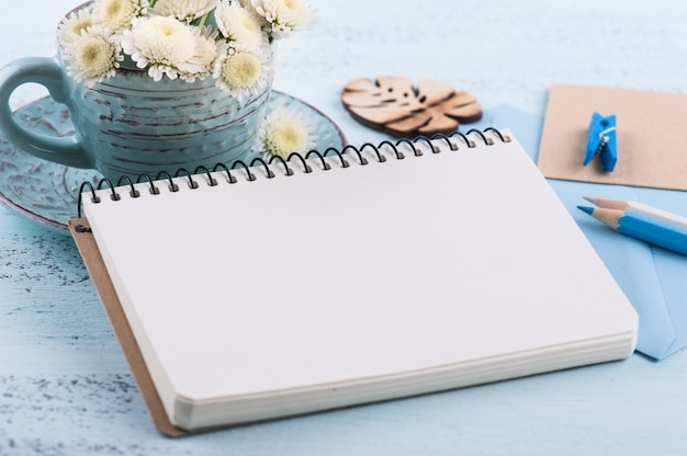 Empty notepad with white chrysanthemum