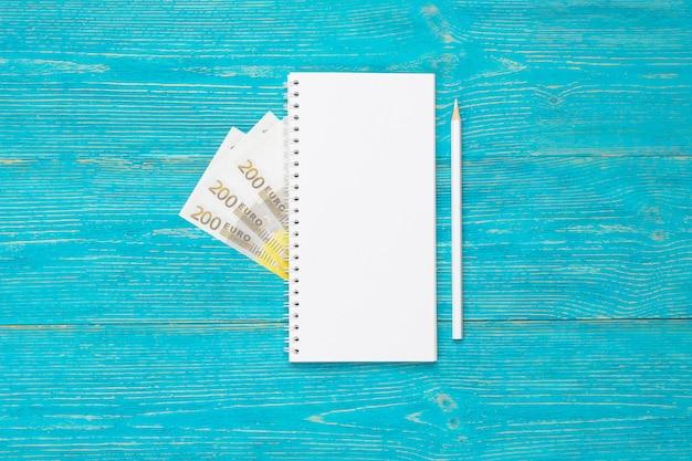 Пустой блокнот с белым карандашом и 200 евро банкнот на бирюзовом деревянном столе, копией пространства