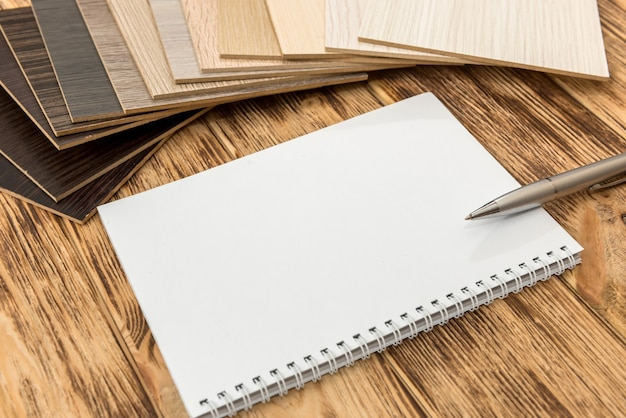 あなたの家の新しいデザインのための木製の床カタログ付きの空のメモ帳。インテリア装飾用の厚板ラミネートコレクション