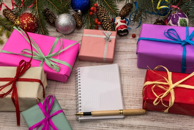 Empty notepad on wooden table with gift boxes and fir branches. planning concept